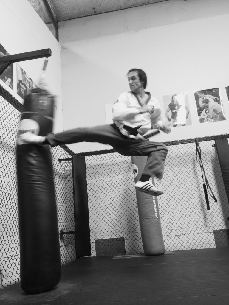 Justin Warren Taekwondo Central Bunbury Instructor excecutes a jump back kick at 43 years of age - B & W