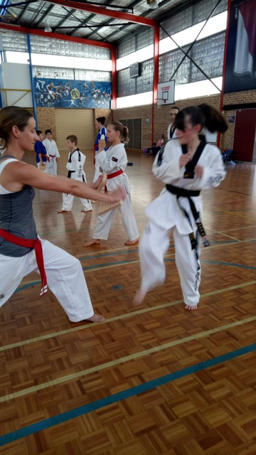 Board Breaking Seminar - Maddison Booth demonstrates her awesome power by smashing a board held by Kelly Platts - www.tkdcentral.com