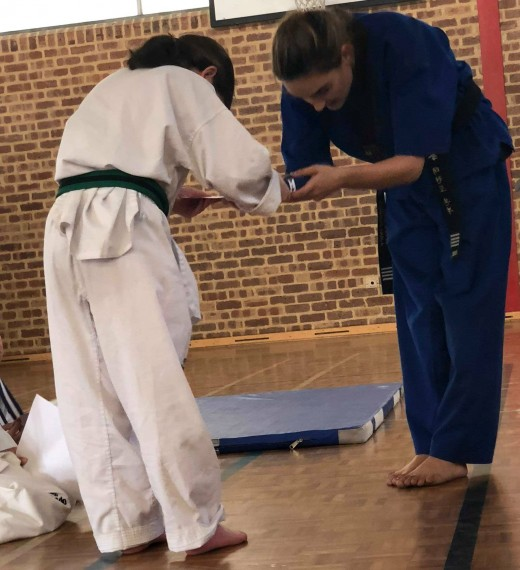 Krystal Ritchie recieves her belt and certificate from Head Instructor Ajana Plunkett at SHP2018 grading