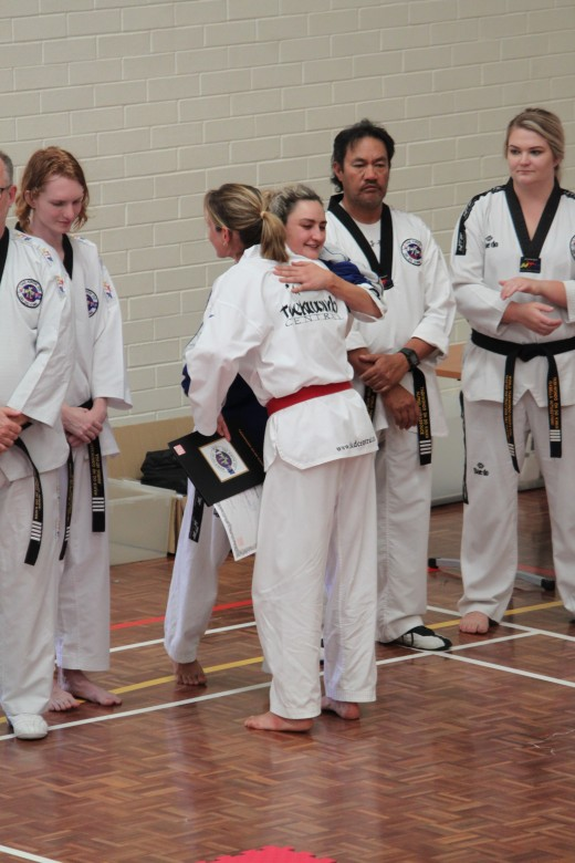 Head Instructor Ajana Plunkett Embraces New Black belt And Best Grading Award Winner Kelly Rowe - www.tkdcentral.com