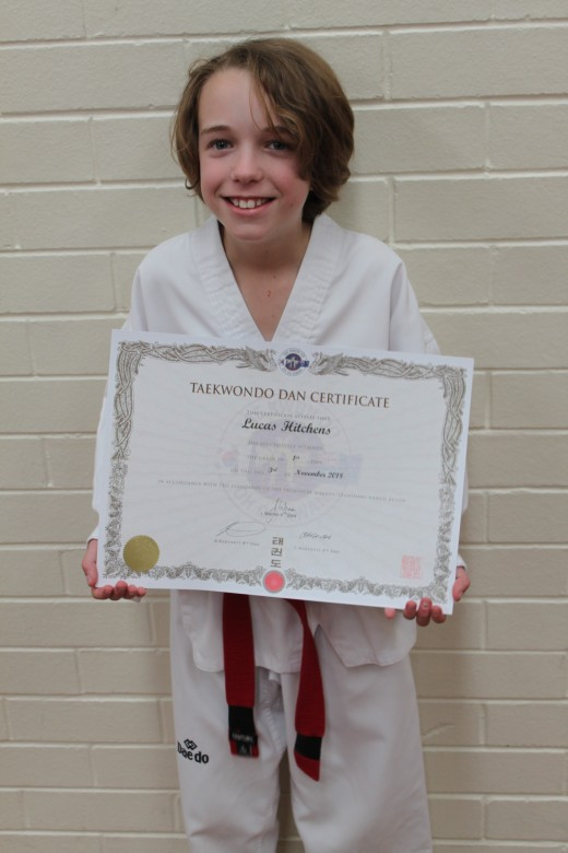 Lucas Hitchens Proudly Holds His 1st Dan Black Belt Certificate - www.tkdcentral.com
